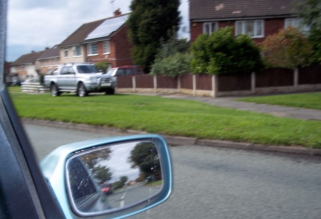 """In the rear view"": Through my wing mirror I can see the erstwhile site of Red House Farm.  Those who farmed there are still commemorated, if you look for the evidence."