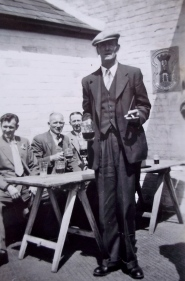 Dressed up to the nines on a club outing...How tall he is!  There's a swagger stick under his arm.  The young officers he encountered during the first war are duly ridiculed...to the entertainment of all.